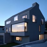 Neoteric facade design of House F presenting jutted out windows and garrage doors (2)