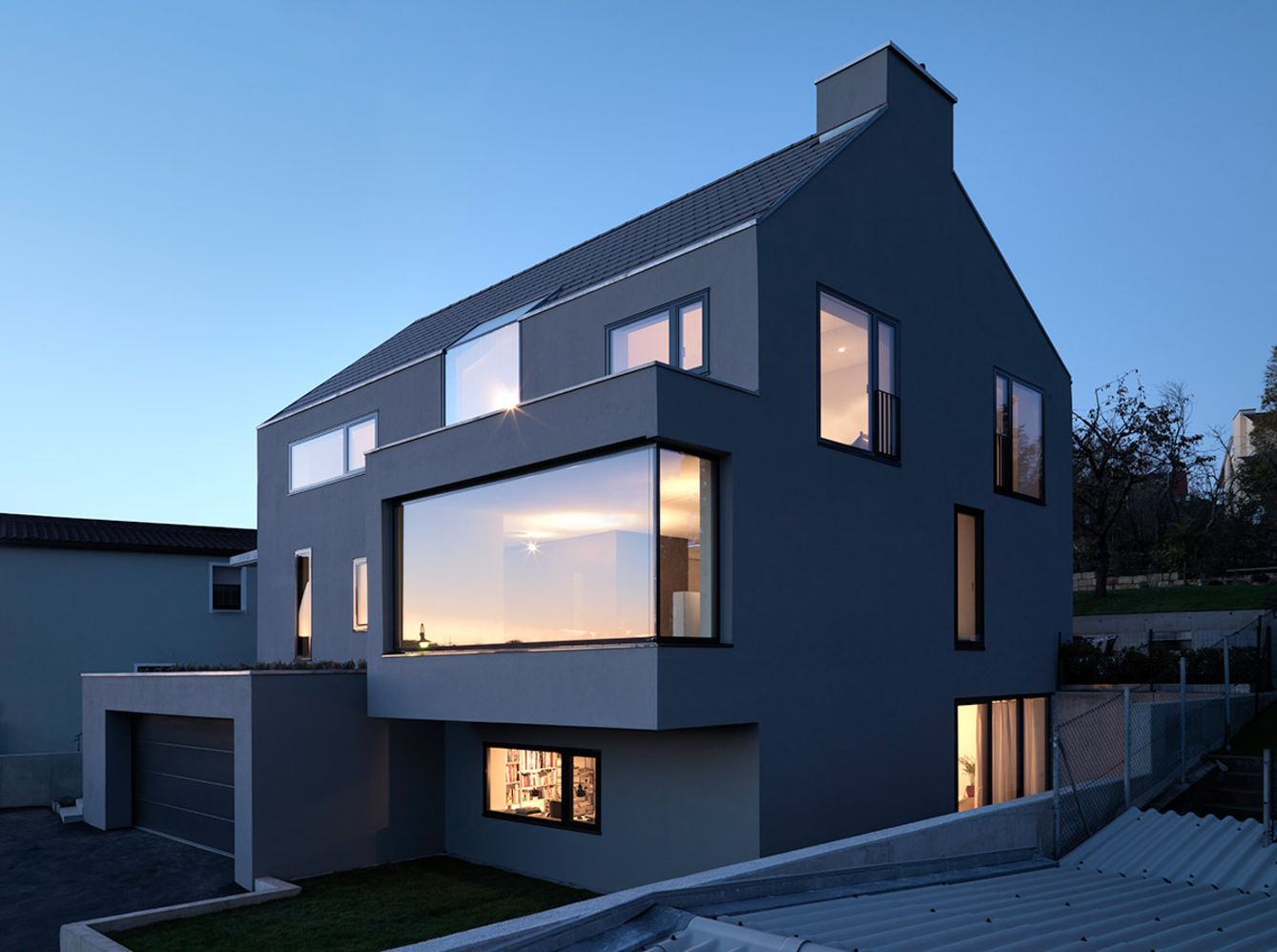 https://elonahome.com/wp-content/uploads/2020/12/Neoteric-facade-design-of-House-F-presenting-jutted-out-windows-and-garrage-doors-2.jpg